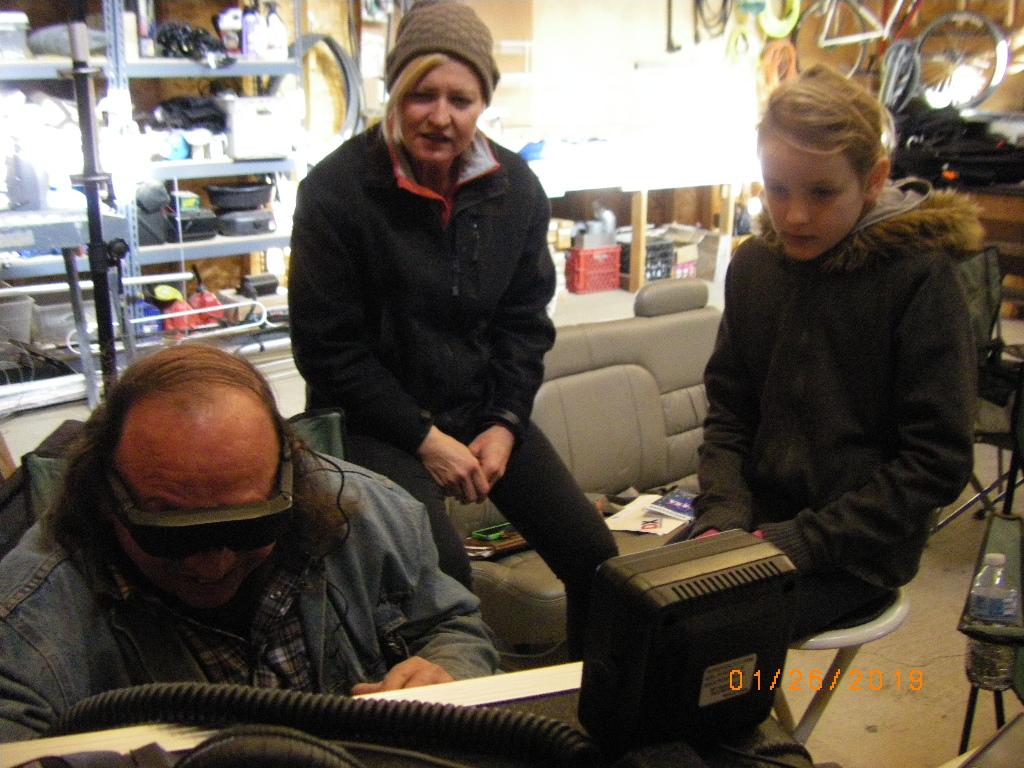 Deb and AJ watching Dan setup the radio